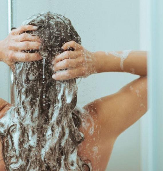 chica lavandose pelo ducha