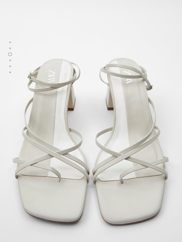Sandalias de tacón de piel color blanco con tiras finas cruzadas y posición para el dedo.