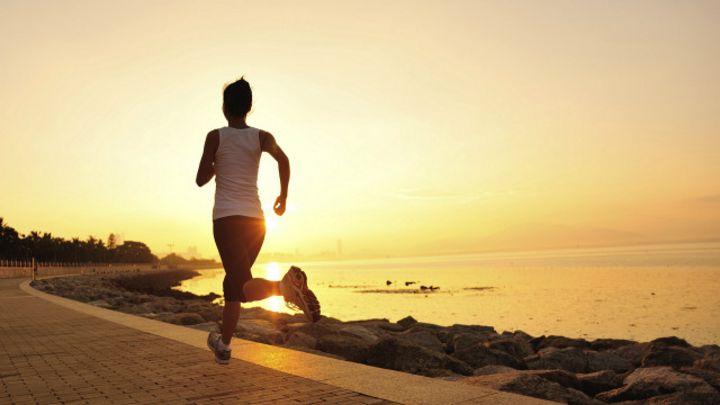 Mujer haciendo ejercicio en la playa al amanecer.