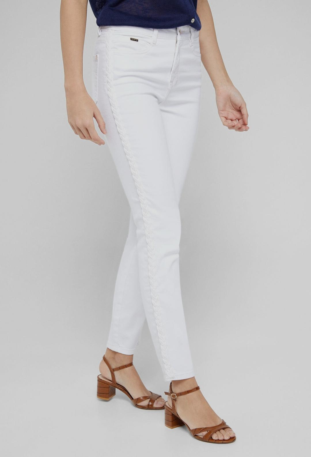 Pantalón pitillo de tiro medio. Detalle de trenzas en las costuras laterales. Prenda confeccionada mediante lavado sostenible.