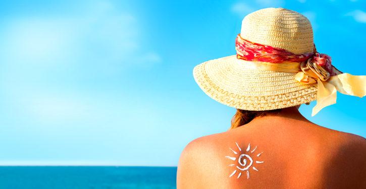 Mujer con sombrero mirando hacia el mar.