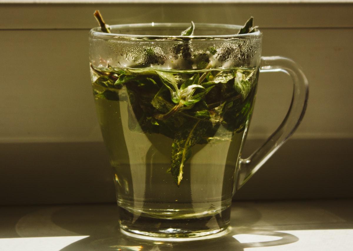 té verde de hoja entera en taza transparente