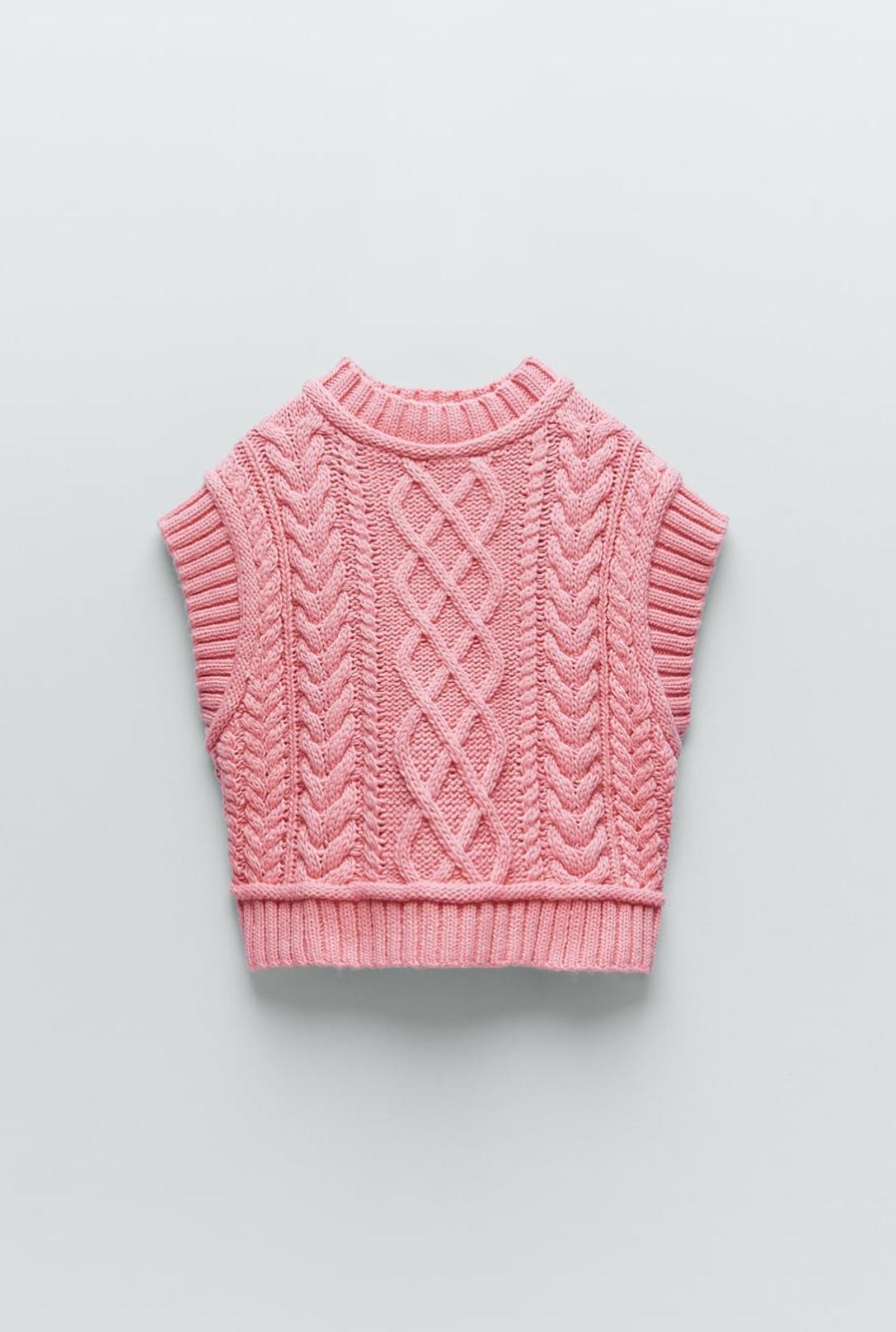Chaleco de punto trenzado con cuello subido y manga sisa en color rosa chicle, de Zara (29'95€)