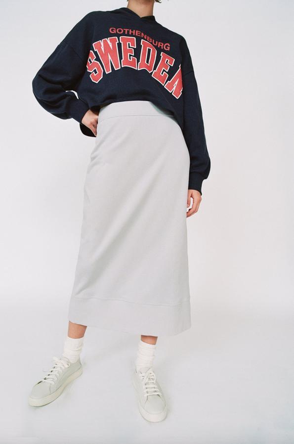 Falda midi de tiro alto y cintura elástica bajo con abertura espalda de Zara.