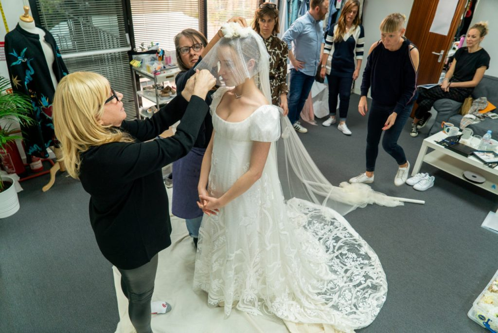 La protagonista en una de las tantas pruebas de vestuario donde luce el vestido de boda, mientras las estilistas le hacen unos arreglos en el velo