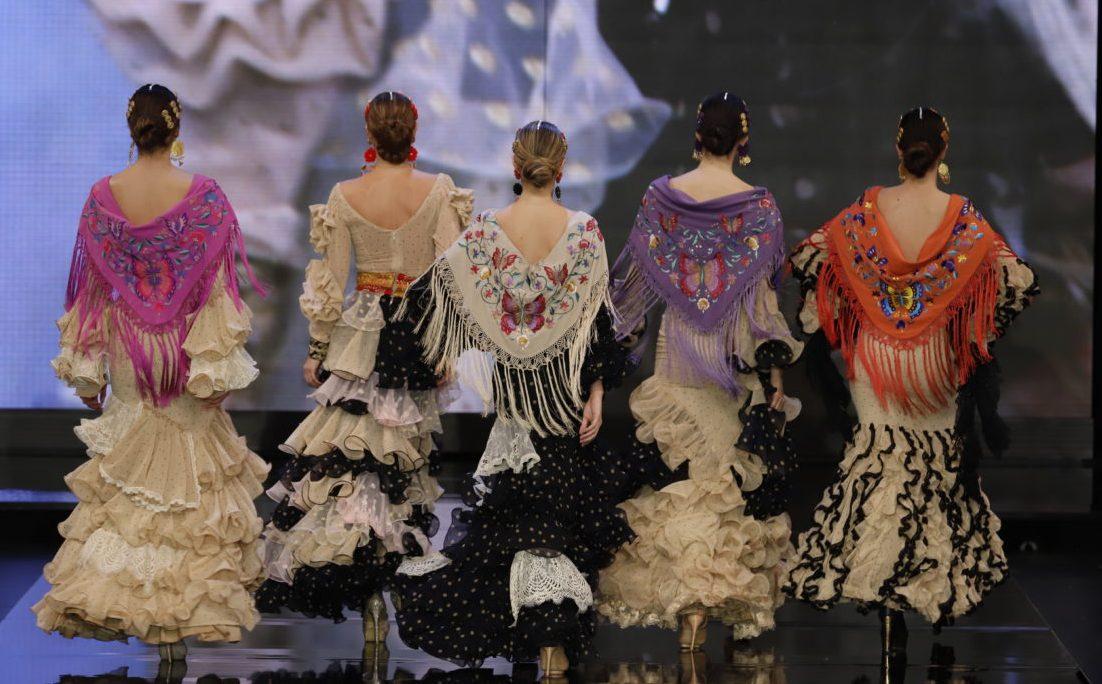 Varias modelos con trajes de flamenca en la pasarela de espaldas