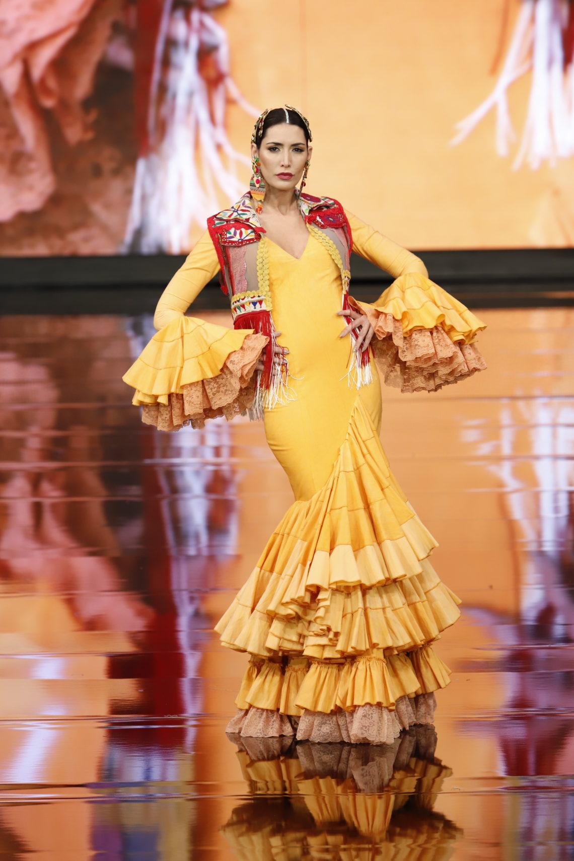 Flamenca en la pasarela con traje amarillo y chaleco granate